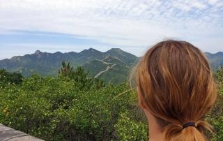 Breena steht auf der Chinesischen Mauer und hat einen super Blick auf die Landschaft.